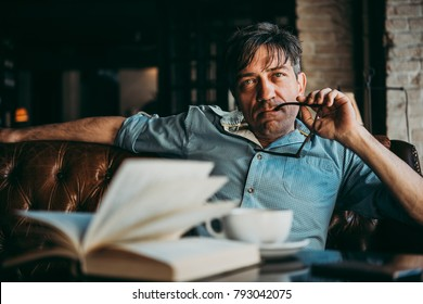 Portrait of a mature confident handsome man while thinking. Book and cup of coffe in front
