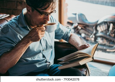 Portrait of a mature confident handsome man reading a book and enjoying his coffee.