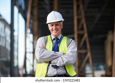 Portrait mature construction engineer man smiling confident with arms crossed site manager wearing hard hat and reflective vest in city