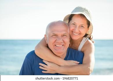 Portrait of mature couple against sea