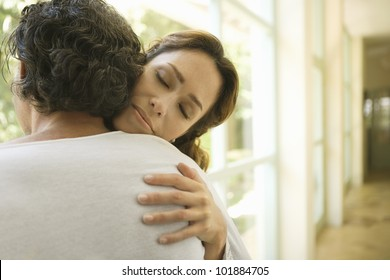 Portrait of a mature couple hugging by large glass doors at home.