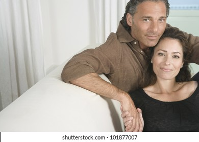 Portrait of a mature couple lounging on a sofa at home and holding hands.