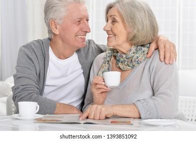 Portrait of mature couple with magazine drinking tea