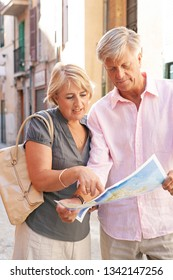 Portrait of mature couple reading map in old city street on holiday, sightseeing together in sunny outdoors. Senior people travel leisure recreation lifestyle, discovery retirement activities.