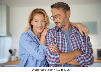 Portrait of mature couple standing in home kitchen