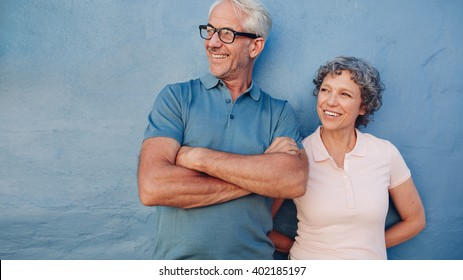 Portrait of a mature couple standing together and looking away and smiling against blue background. Middle aged man and woman leaning to a wall.