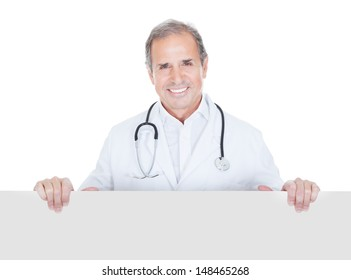 Portrait Of Mature Doctor Holding Placard Over White Background