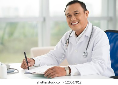 Portrait of mature doctor sitting in his office and looking at camera