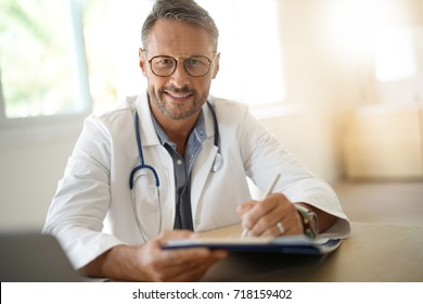 Portrait of mature, doctor sitting in medical office