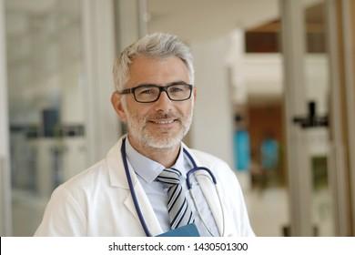 Portrait of mature doctor standing in hospital hallway