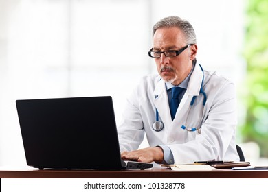 Portrait of a mature doctor using his laptop computer