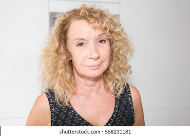 portrait of mature elderly woman blonde and curly retired