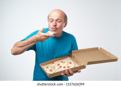 Portrait of mature european man eating a slice of pizza. In his hands he holds a box of food. Studio shoot. concept of eating fast food at old age