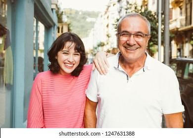 Portrait of a mature father with his young daughter laughing on the street. Focus on him