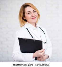 portrait of mature female doctor or nurse with clipboard over white brick wall