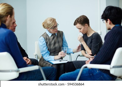 Portrait of mature female mentor guiding psychological support group comforting young woman with other people attending sitting in circle and sharing their problems