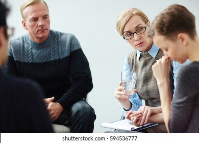 Portrait of mature female mentor wearing glasses guiding psychological support group comforting young woman