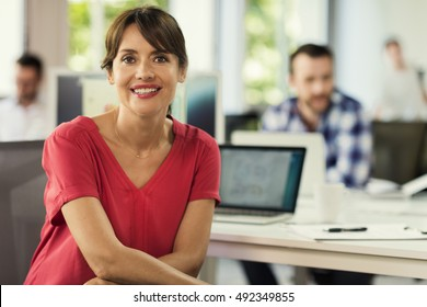 Portrait of mature female in open space company. Smiling business woman in office.