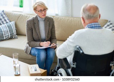 Portrait of mature female psychiatrist interviewing handicapped senior man during therapy session, copy space
