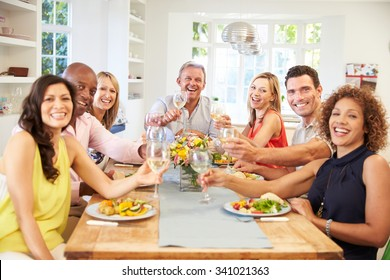 Portrait Of Mature Friends Around Table At Dinner Party