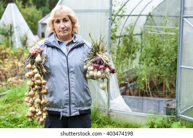 Portrait of mature gardener stands in front of greenhouse with onion harvest in hands, outdoor