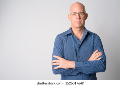 Portrait of mature handsome bald businessman with arms crossed