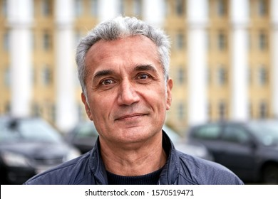 Portrait of a mature handsome friendly man with short silver hair outside. Aged cheerful dentist is standing on the street and posing. Happy senior person outdoors in the fall.