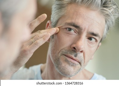 Portrait of mature handsome man looking in mirror at home