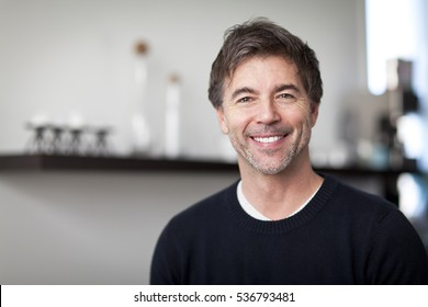 Portrait Of A Mature Handsome Man Smiling At The Camera. Home. Kitchen