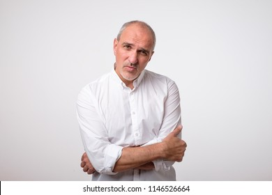 portrait of mature handsome man in white shirt with serious and sad expression on face. Negative facial emotion