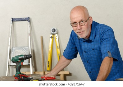 a portrait of mature handyman at DIY workshop