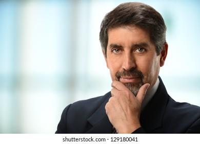 Portrait of mature Hispanic businessman with hand on chin indoors