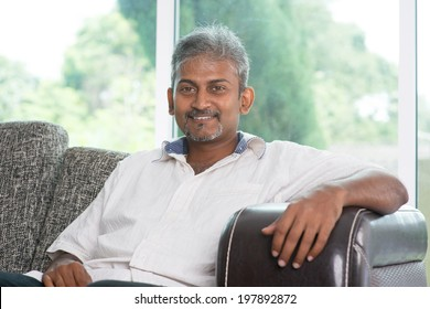 Portrait of mature Indian man sitting on sofa at home. Asian male relax on couch in house with interior.