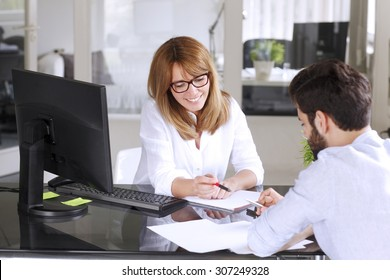 Portrait of mature insurance agent giving advise her new client while sitting at office in front of computer. Businesswoman making financial plan.