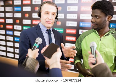 Portrait of mature interpreter translating African-American sportsman giving interview to group of journalists during press conference