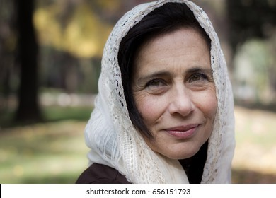 Portrait of mature lady covering her head with hijab style white shawl in the park. Young looking woman with white veil over head, Muslim look. Female model with charming serene look and soft skin