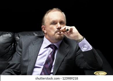 portrait of a mature mafia boss smoking a cigar