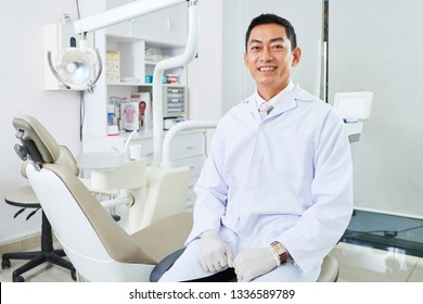 Portrait of mature male dentist in uniform sitting near the empty dental chair and smiling in dentist office