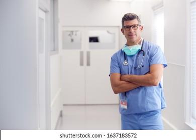 Portrait Of Mature Male Doctor Wearing Scrubs Standing In Hospital Corridor