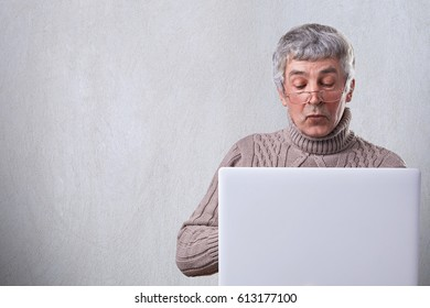 A portrait of mature male with gray hair wearing glasses and sweater having wise expression while working with his laptop at home. Old senior man with computer. People and technology concept.