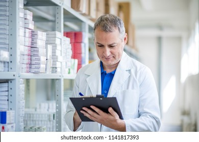 Portrait of mature male pharmacists working in modern drugstore. Medical factory supplies storage indoor with male pharmacists. Pharmacist man in the warehouse holding boxes with drugs in hands