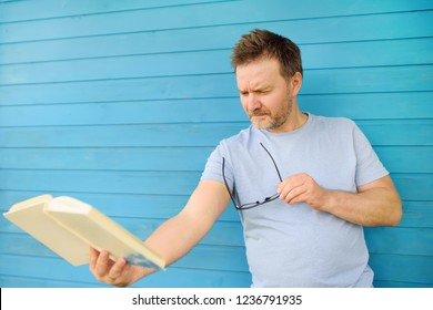Portrait of mature man with big black eye glasses trying to read book but having difficulties seeing text because of vision problems. Hyperopia, presbyopia.