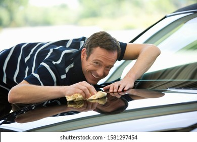 Portrait of mature man cleaning and polishing car with pride