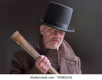 Portrait of a mature man dressed as a sinister Victorian criminal holding a wooden bat