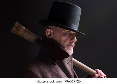 Portrait of a mature man dressed as a sinister Victorian criminal, holding a wooden bat