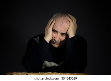 Portrait of mature man enfolded his head with palms while sitting at the table