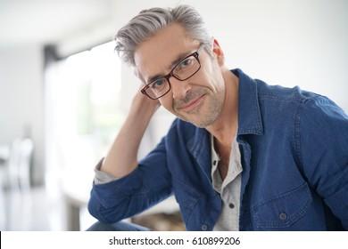Portrait of mature man with eyeglasses sitting on sofa