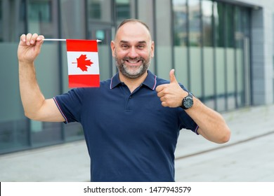 Portrait of a mature man with the flag of Canada shows thumb up gesture on the background of an office building. Good business is a Canadian entrepreneur.