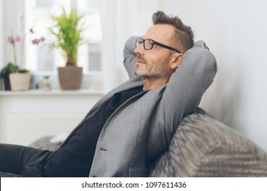 Portrait of mature man with glasses wearing grey jacket relaxing on sofa