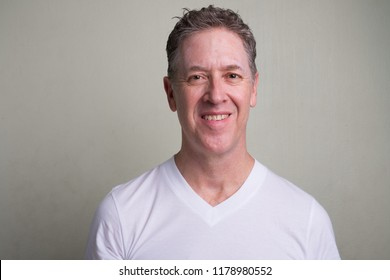 Portrait of mature man with gray hair against white background